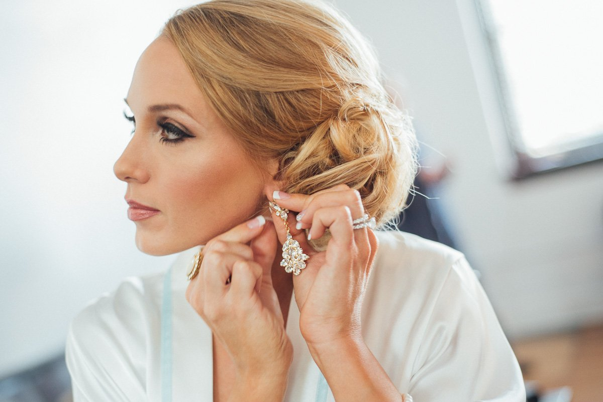 bride putting her earrings on at victory arts center in fort worth