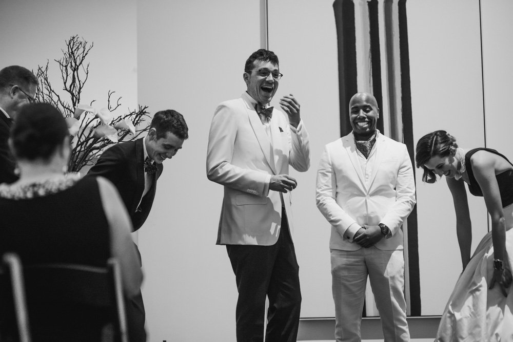 bride and groom and best man dissolve in laughter during an intimate moment at a blanton museum of art wedding in austin, summer wedding at blanton museum of art