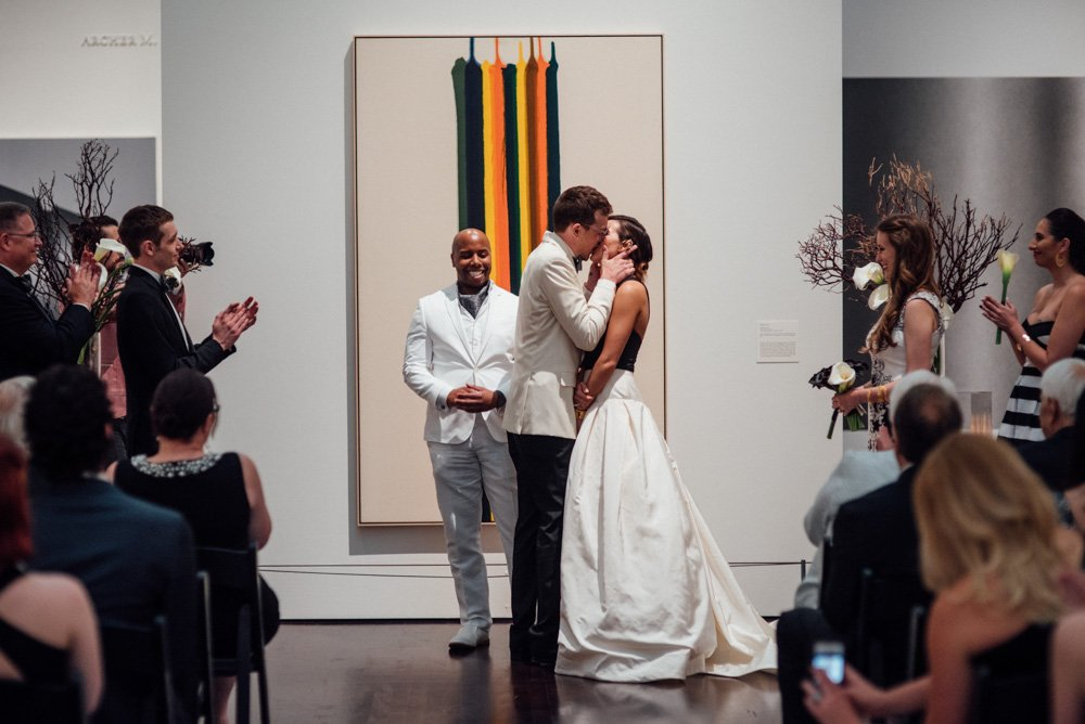 first kiss as married couple in blanton museum of art's upstairs gallery, modern wedding at blanton art museum,