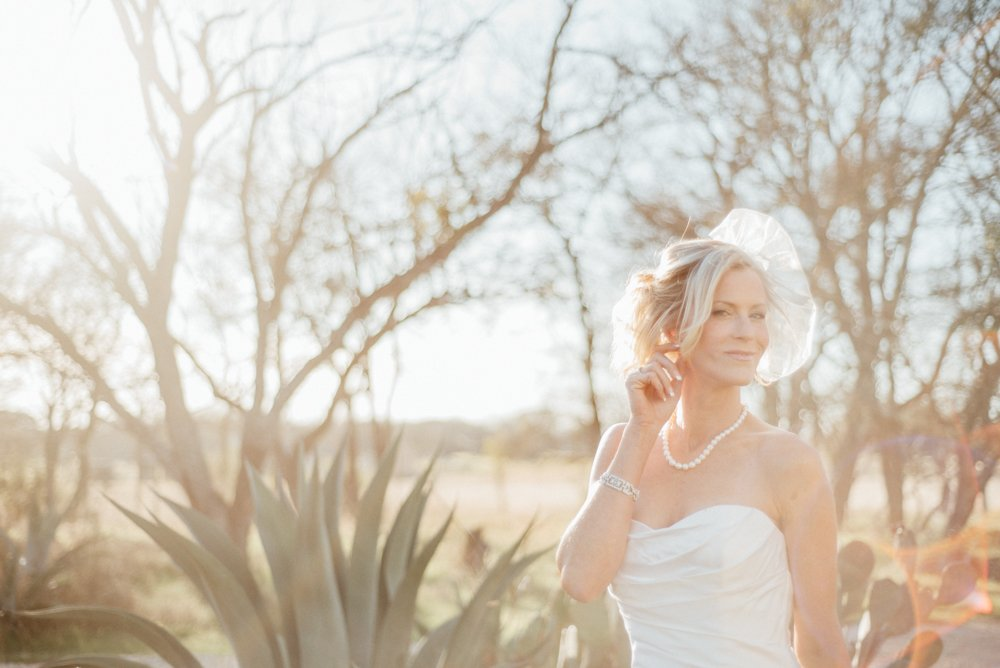 austin bridal portraits with a vintage style birdcage veil backlit with sun flare