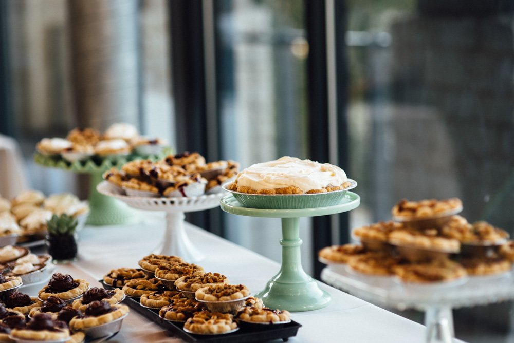 dessert bar of wedding pie, wedding pie at lady bird johnson wildflower center, dessert pie, unique wedding details austin wedding photographer, variety of pies on vintage stands at a wedding in austin texas