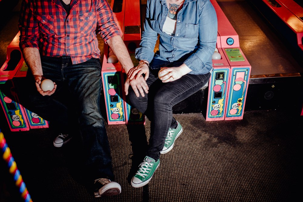 colorful austin nerdy engagement session couple wearing jeans and converse, skee ball engagement session, creative austin engagement session photographer in austin