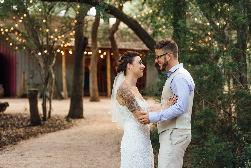 bride and groom do a first look at the wildflower barn in driftwood texas