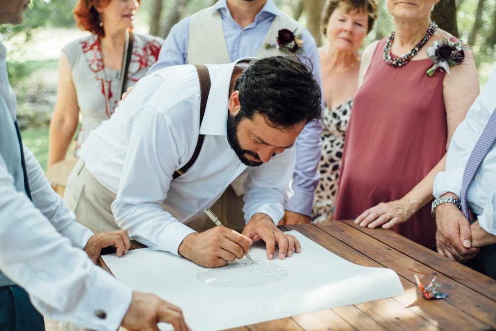 signing the ketubah at an outdoor wedding at the wildflower barn in dripping springs