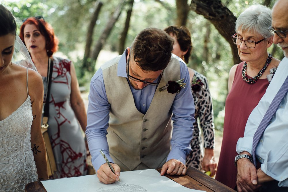groom signs the ketubah at an outdoor summer wedding in austin