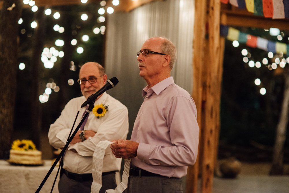 wedding toasts under the fairy lights at the wildflower barn in driftwood