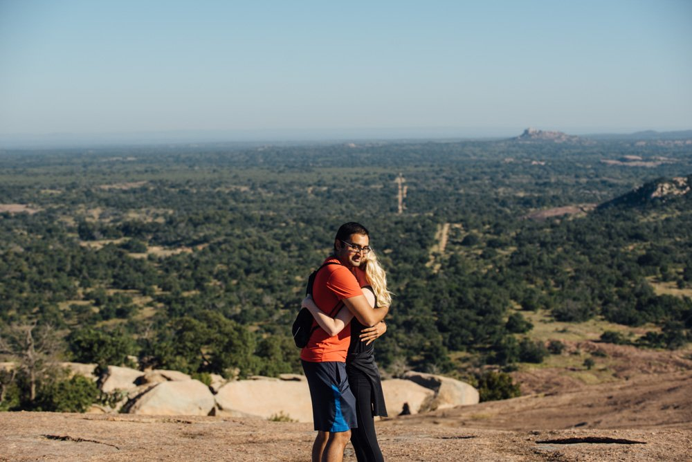 emotional hug between a couple at the top of enchanted rock in austin