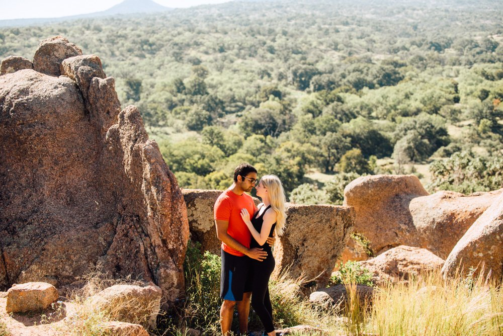 a couple poses for portraits at enchanted rock after their sunrise proposal