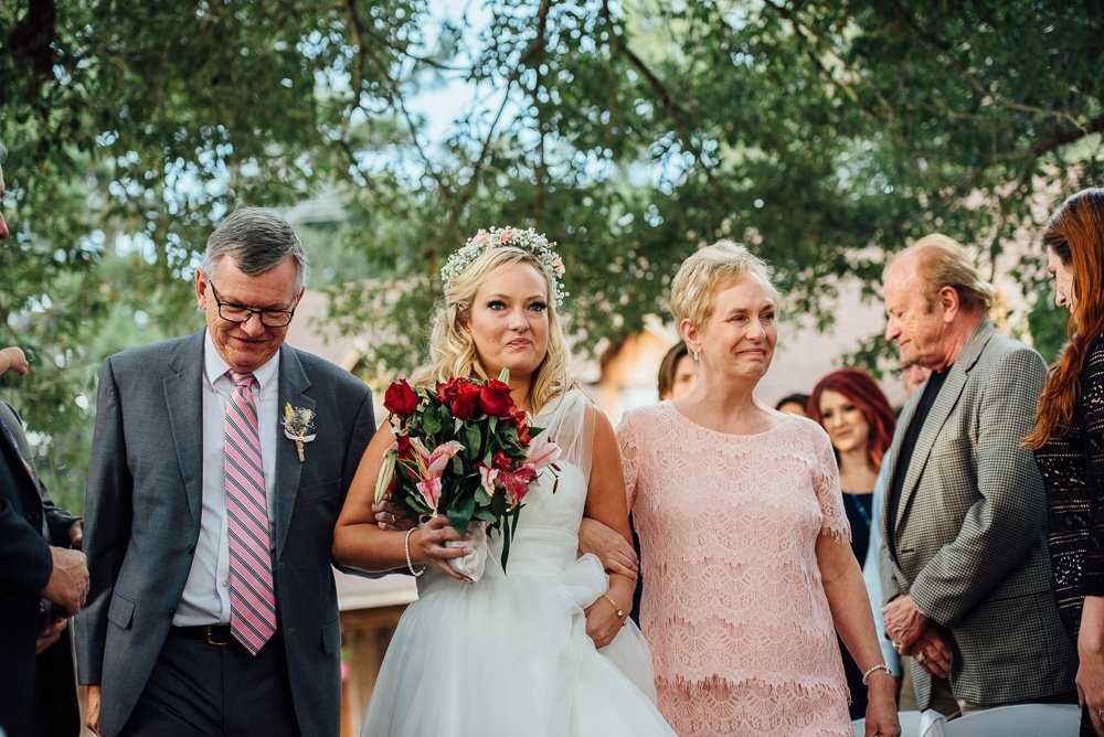 bride walking down aisle with both parents and wearing flower crown