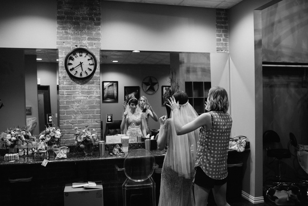 bride putting her veil on at the cotton mill in mckinney