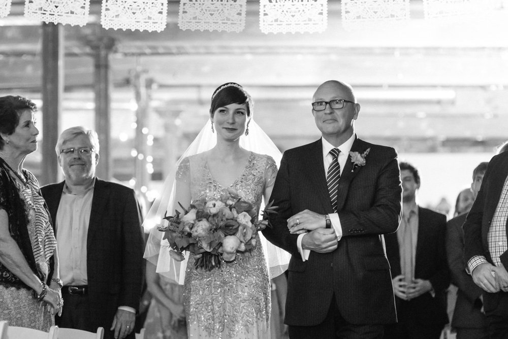 bride walks down the aisle with her dad at a mckinney cotton mill wedding