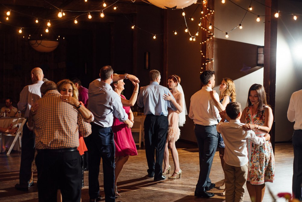 bride in a short pink dress dances at her mckinney cotton mill reception