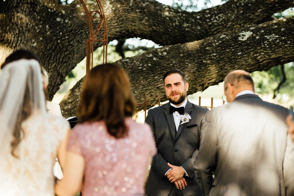 groom cries as he sees his bride walk down the aisle at a fall wedding in texas