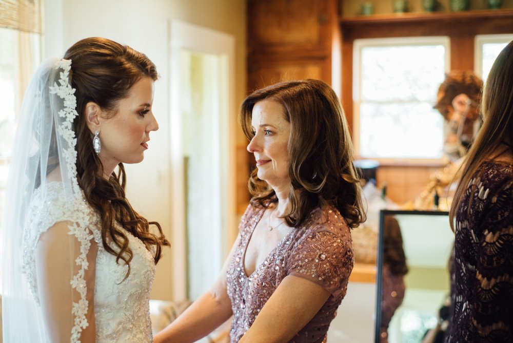 mother of the bride looks at her daughter emotionally at a river rock event center wedding