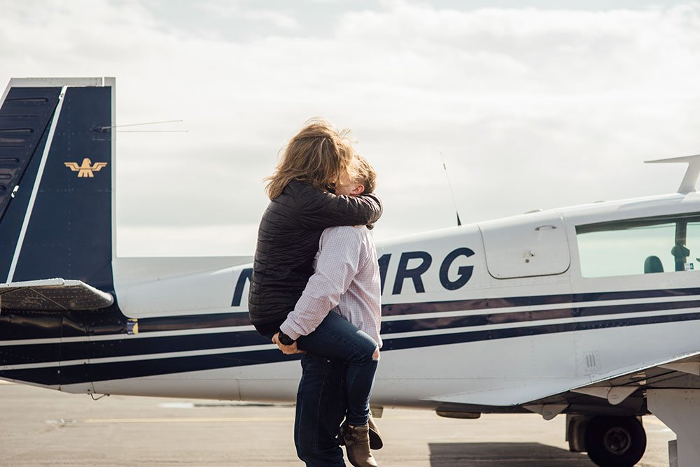 girl hugging guy after he proposed to her in a private airplane ride