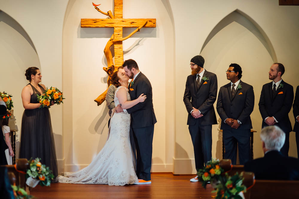 first kiss at heritage house, groomsmen in converse, orange and green wedding colors, romantic indoor wedding in austin texas, austin intimate brunch wedding photographer, intimate brunch wedding, first kiss at a wedding