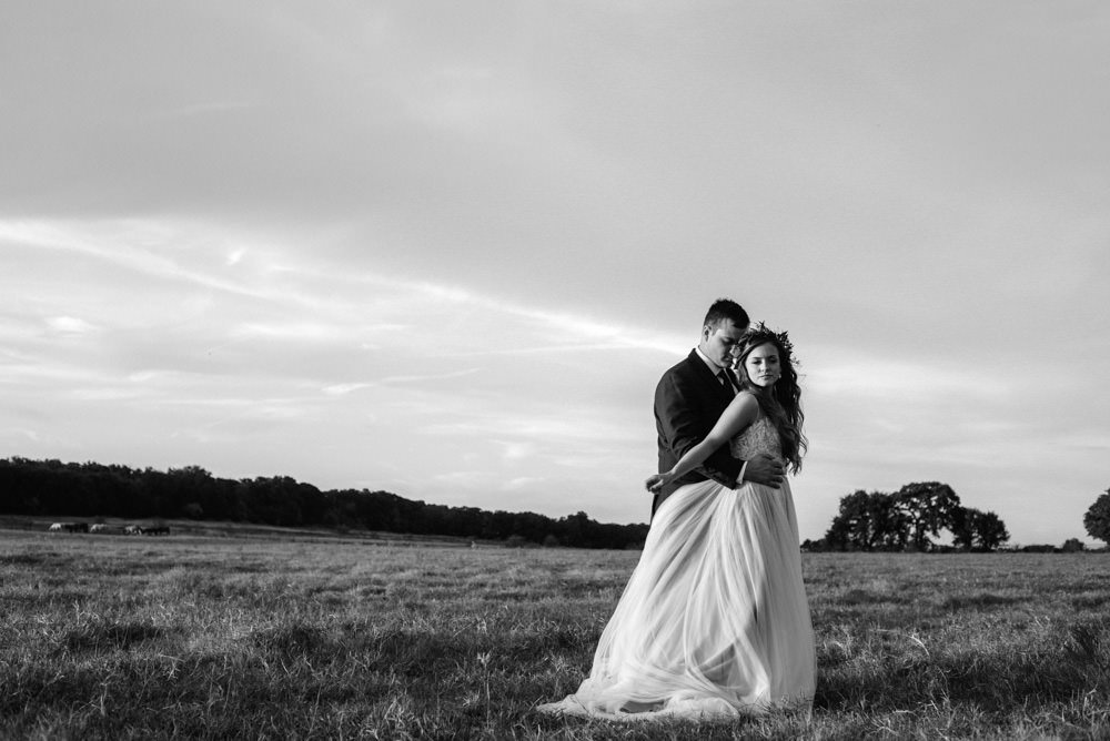 dramatic black and white portraits of bride and groom in a field