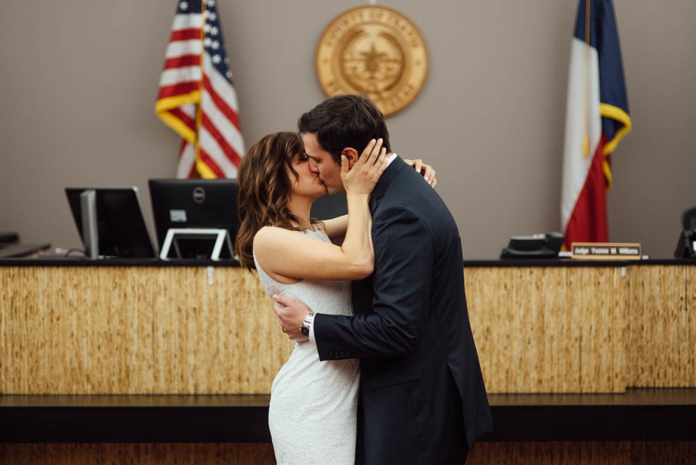 first kiss as husband and wife after a short, intimate elopement in an ugly courthouse room with fluorescent lighting and computers