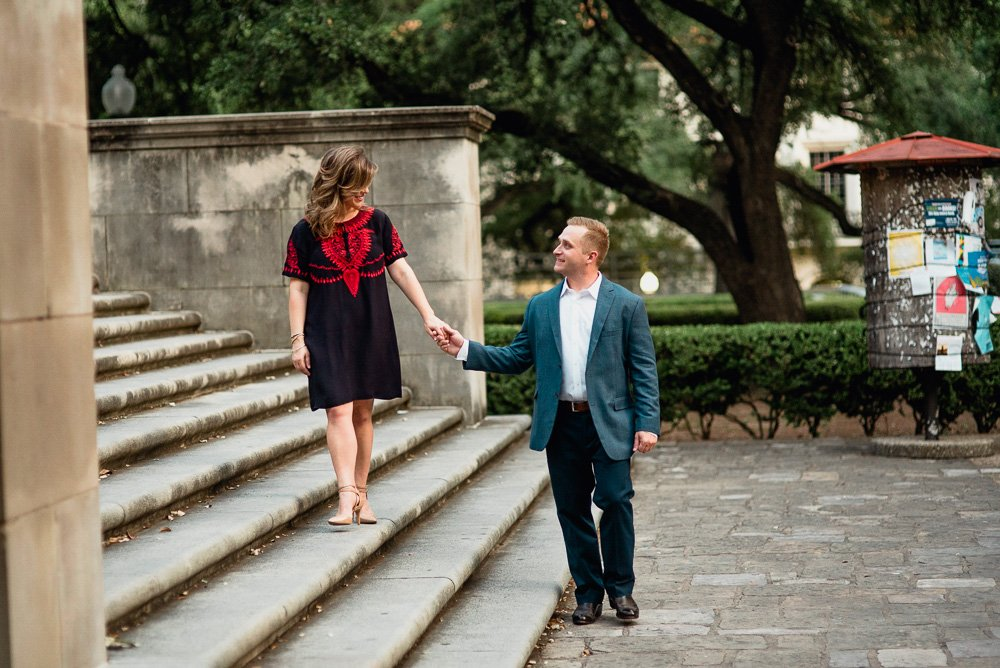 a couple walks hand in hand along a staircase during their UT campus engagement photographs