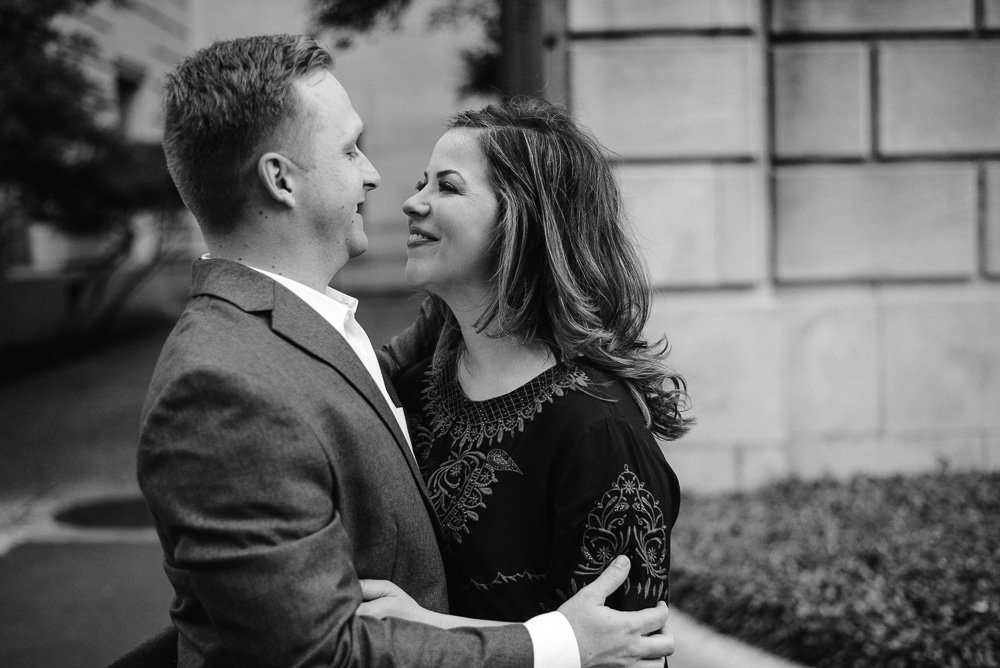 black and white photograph of a candid moment during a couples engagement session on the UT campus