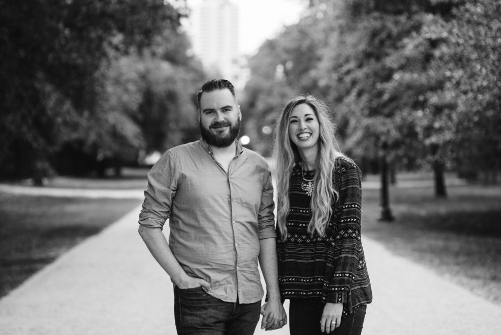 black and white portrait of a smiling happy couple on a tree lined boardwalk in spring, romantic engagement session photographer, romantic engagement session photography