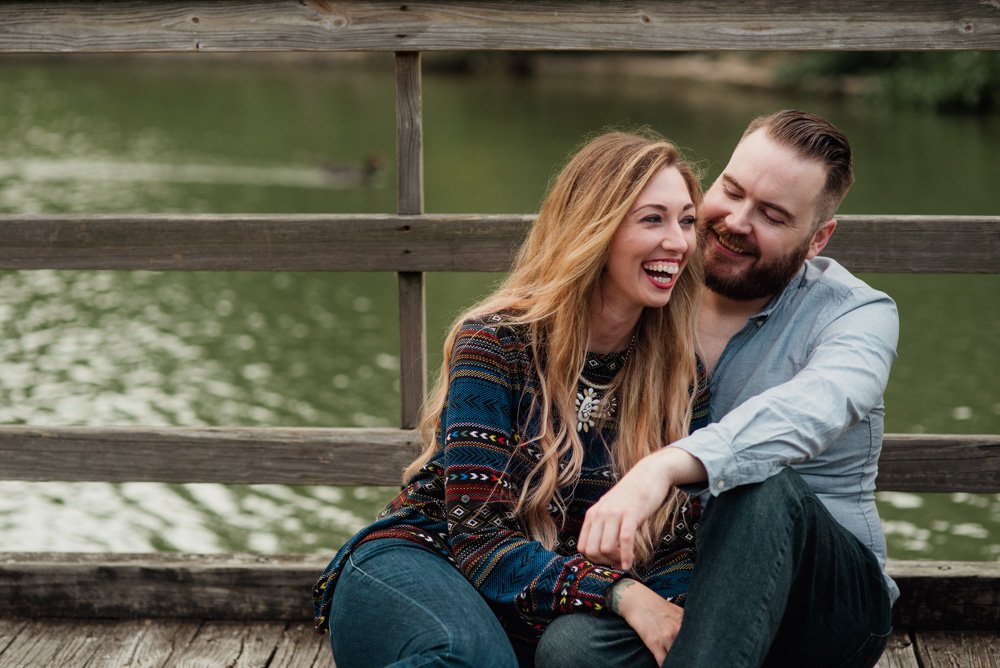 laughing couple on a wooden bridge, houston engagement portraits on a bridge, houston park engagements, nature engagement session in houston, hermann park engagement photos, natural locations for engagement portraits