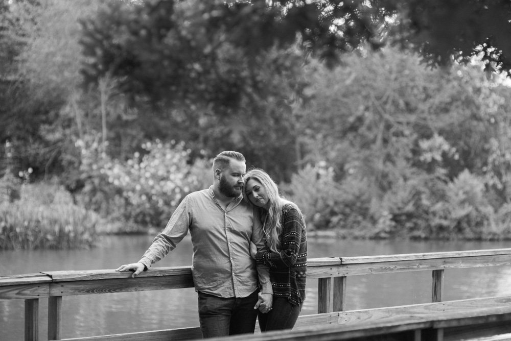 couple on a park boardwalk snuggling for engagement photos in central houston