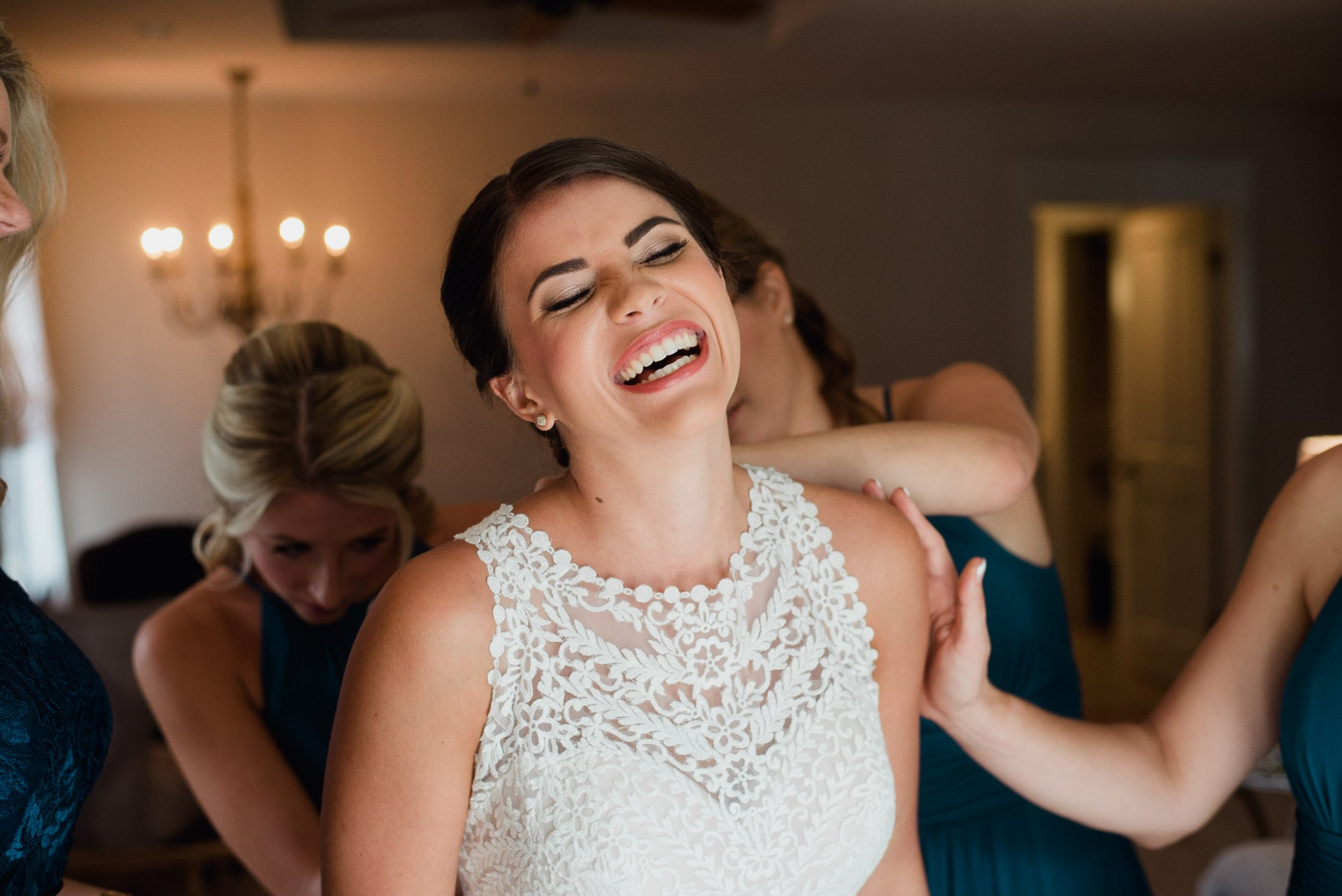 bride laughing while her bridesmaids get her dressed