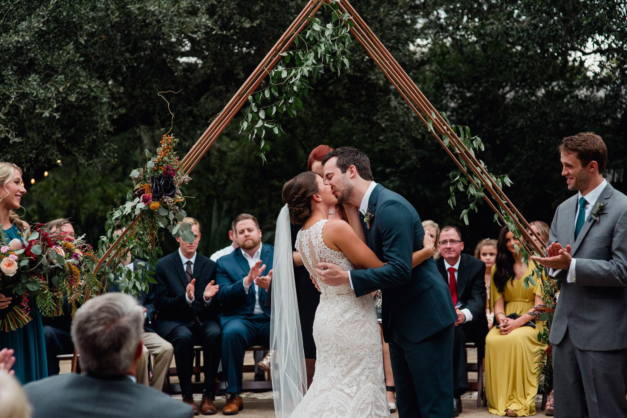 first kiss under a copper triangular arch decorated with flowers at the greenhouse at driftwood, central texas wedding vendors, non-traditional austin wedding photography, colorful and timeless wedding photos in austin, professional wedding photographers in austin texas