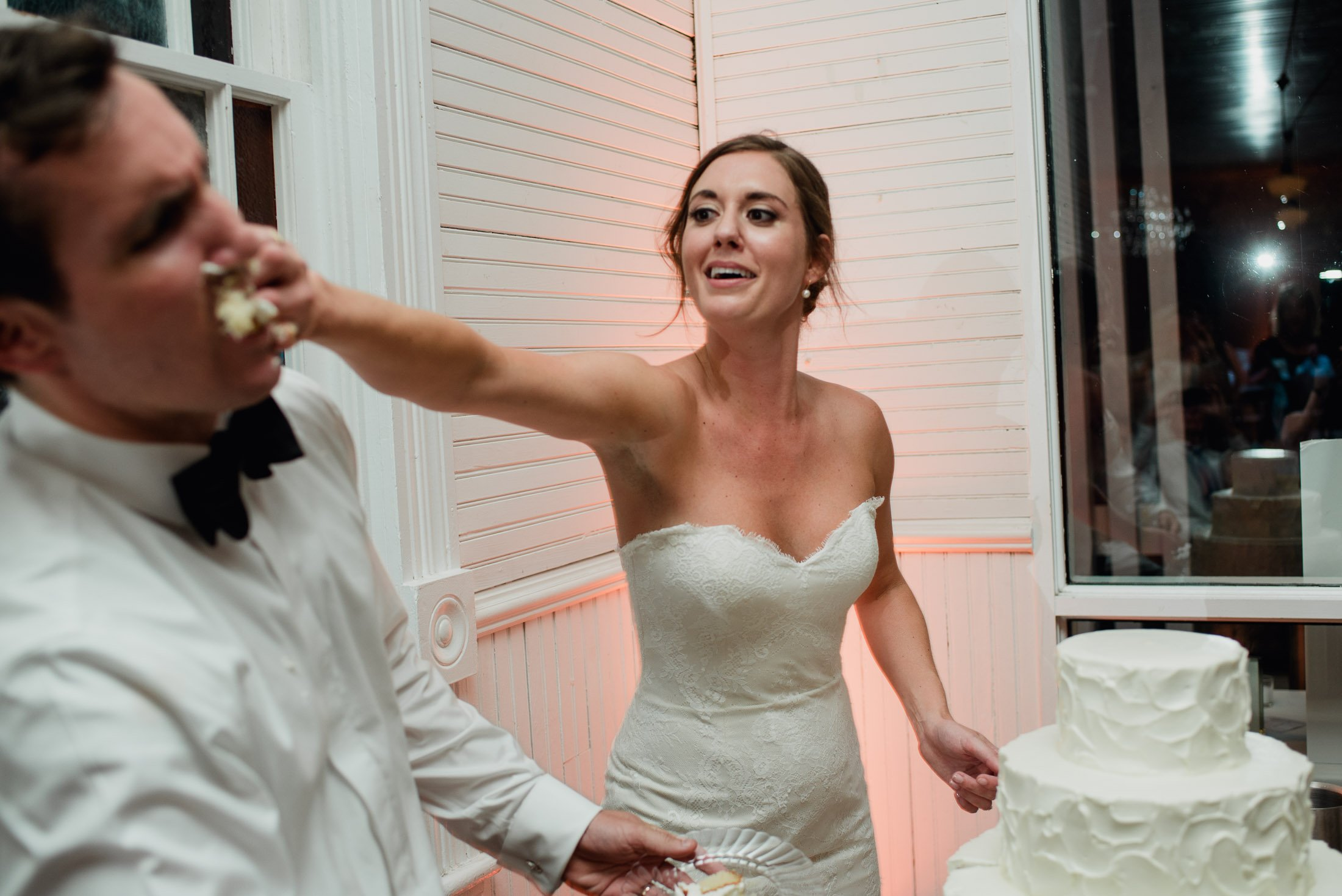 color photograph of a cake cutting bride smashing cake into groom's face at a mercury hall wedding in austin texas