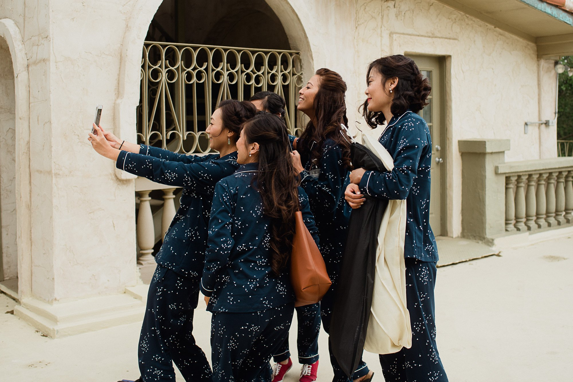 bride and bridesmaids taking a selfie together before getting ready