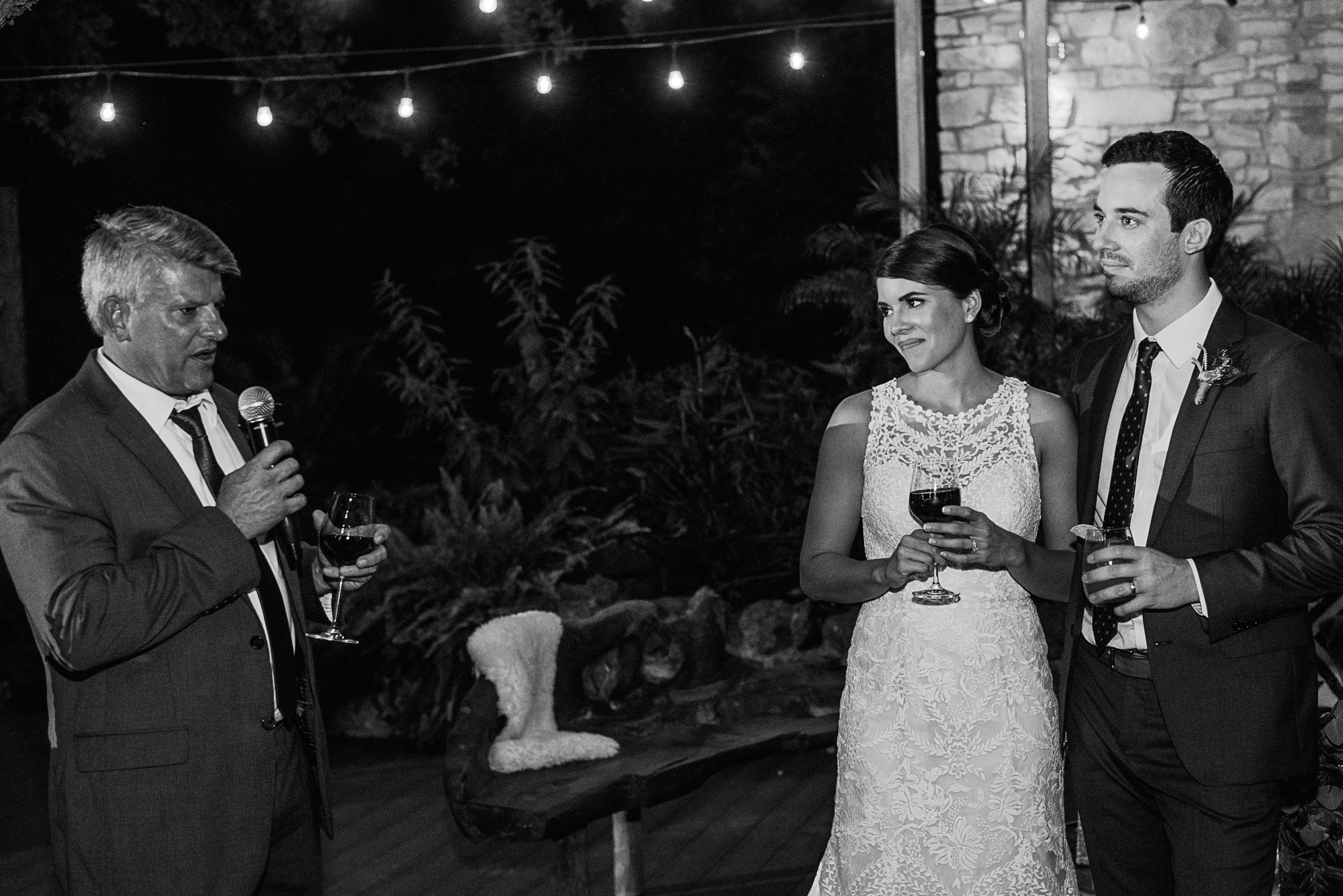 wedding toasts outdoors under string lights