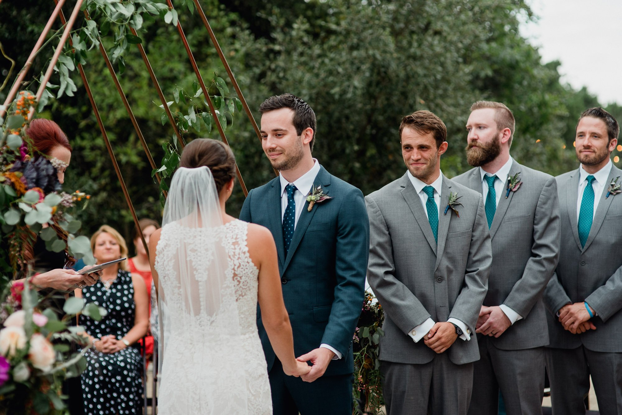 groomsmen smiles at bride during his best friend's wedding