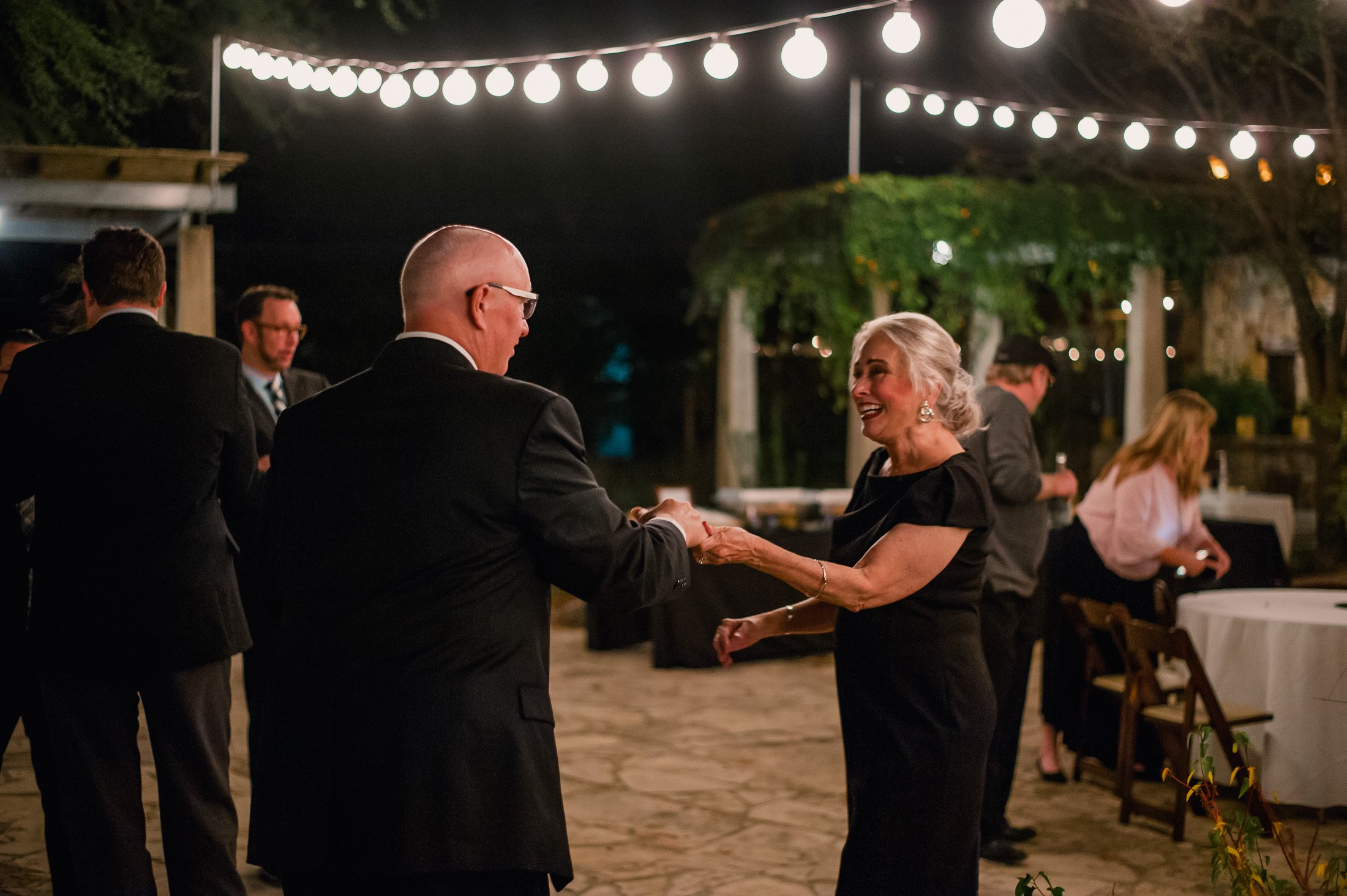 couples dance under string lights at an outdoor austin wedding