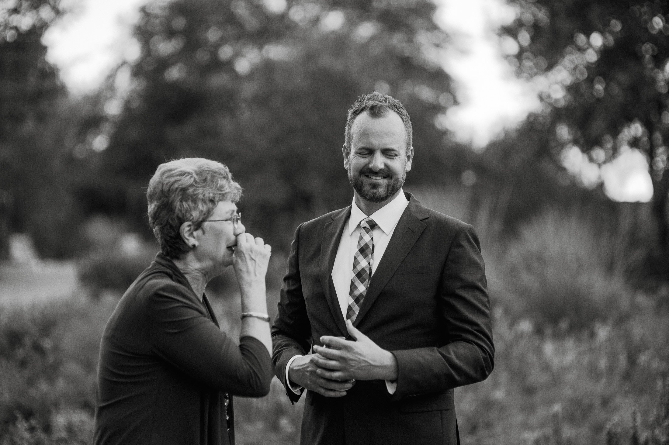 black and white candid of a groom and his mother laughing together at an austin wildflower nature center wedding