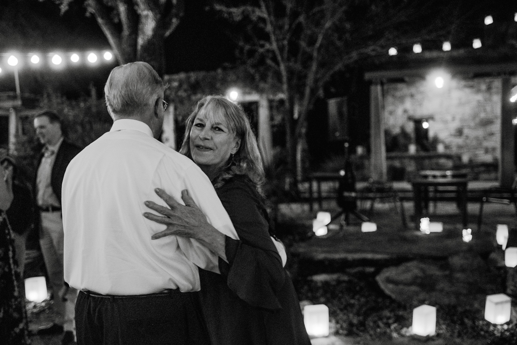 black and white photograph of a couple dancing under the lights at the wildflower center