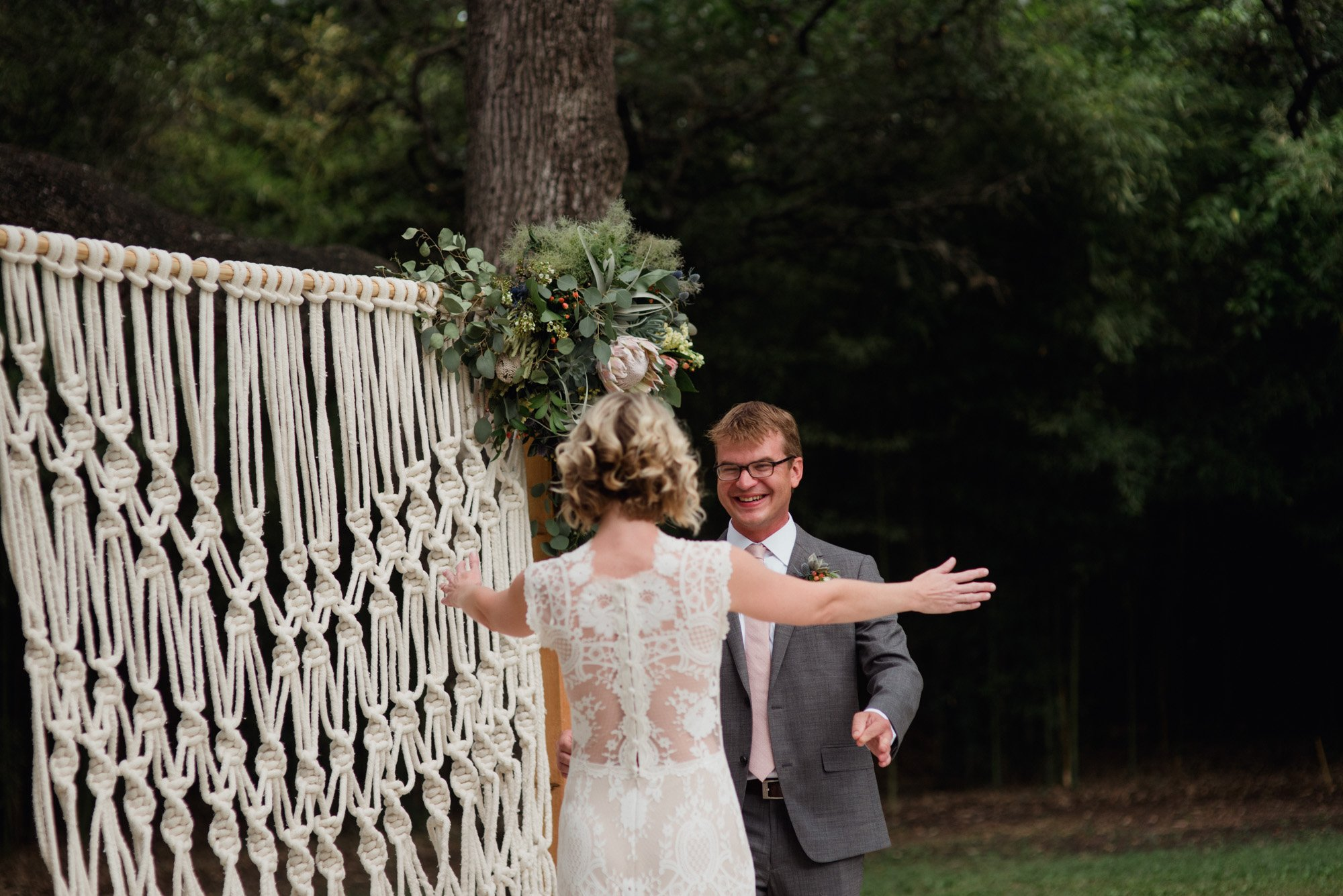 first look in front of a macrame backdrop at a summer wedding in austin texas