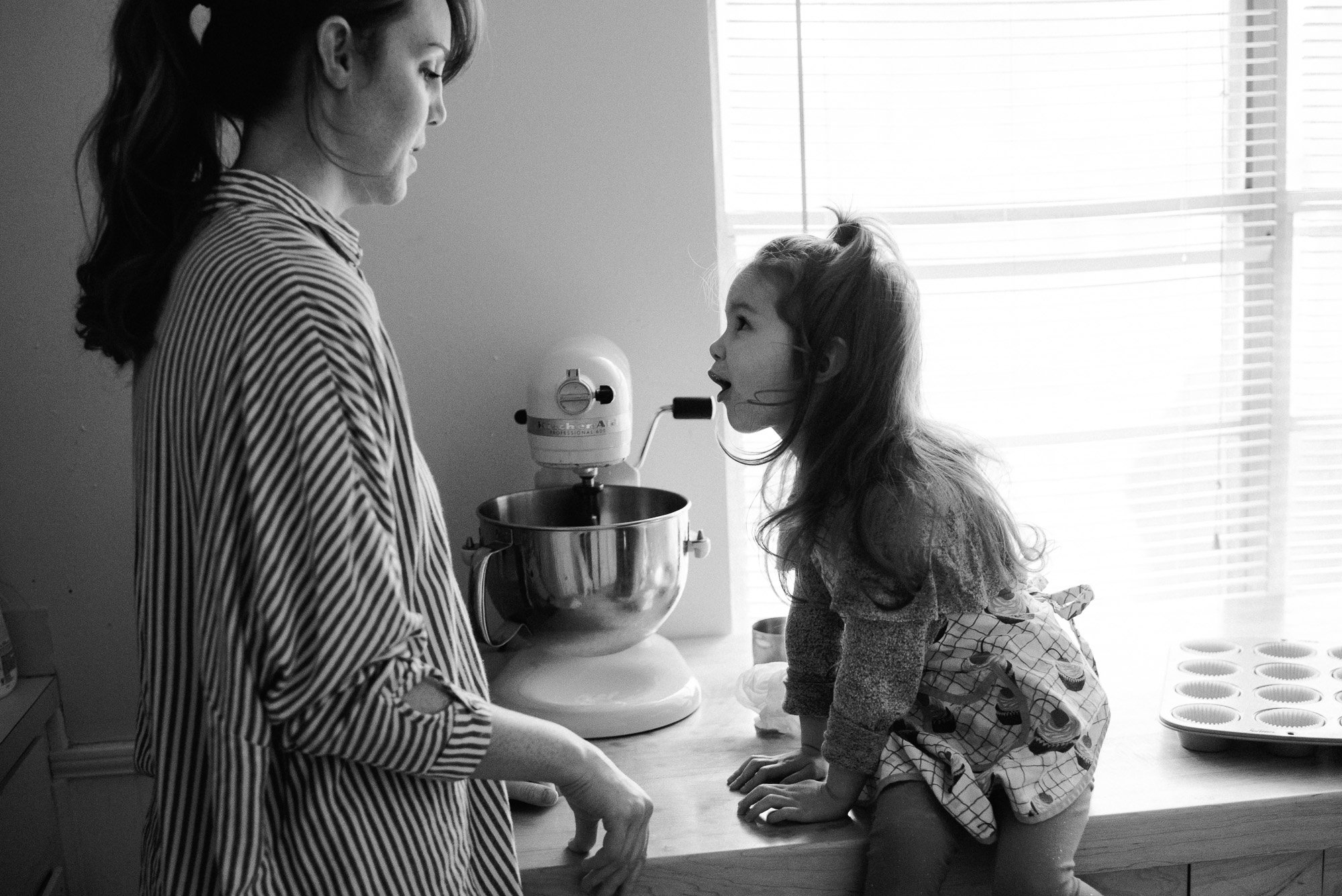 black and white candid shot of a mother and daughter baking