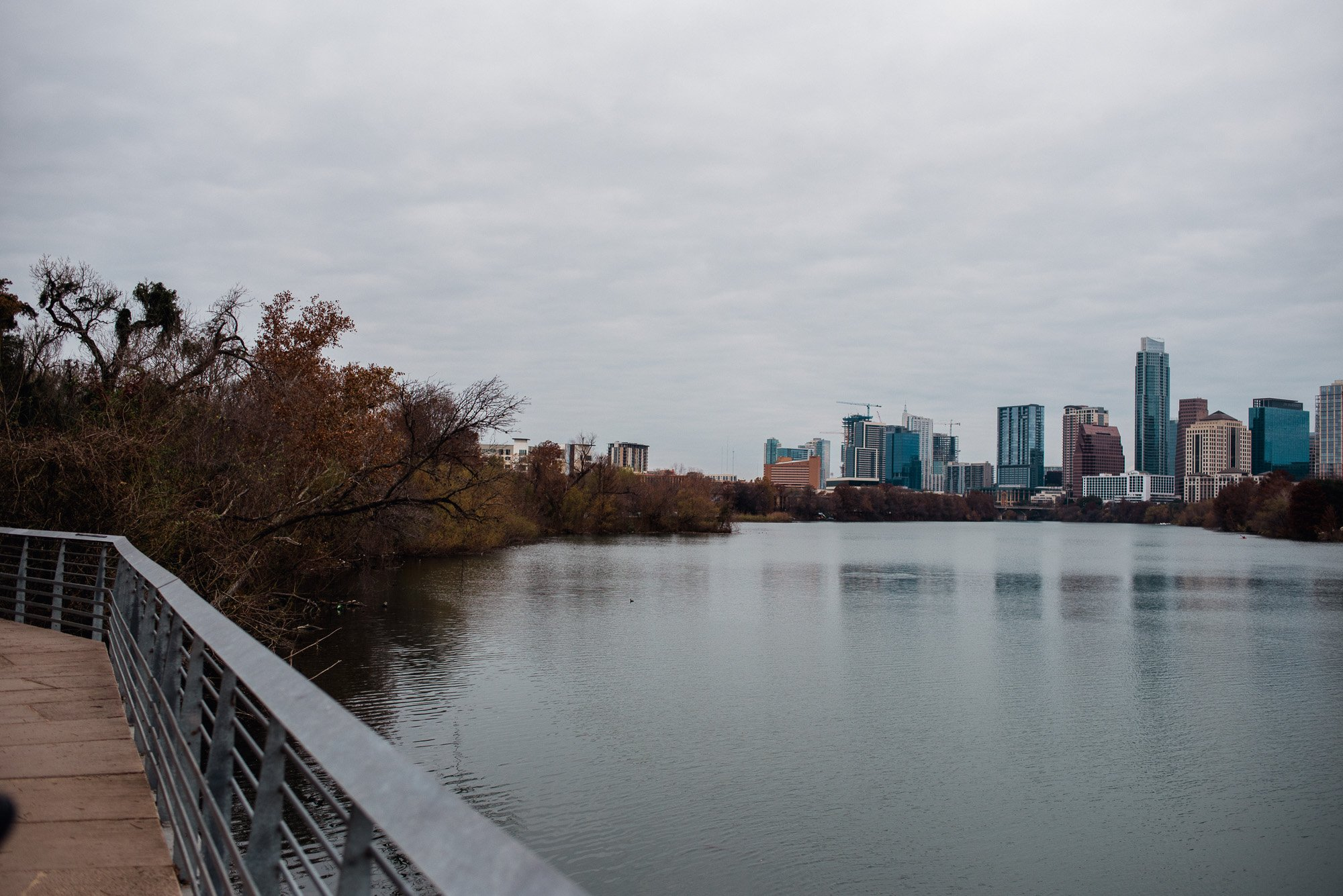 view of downtown austin from the ladybird lake boardwalk