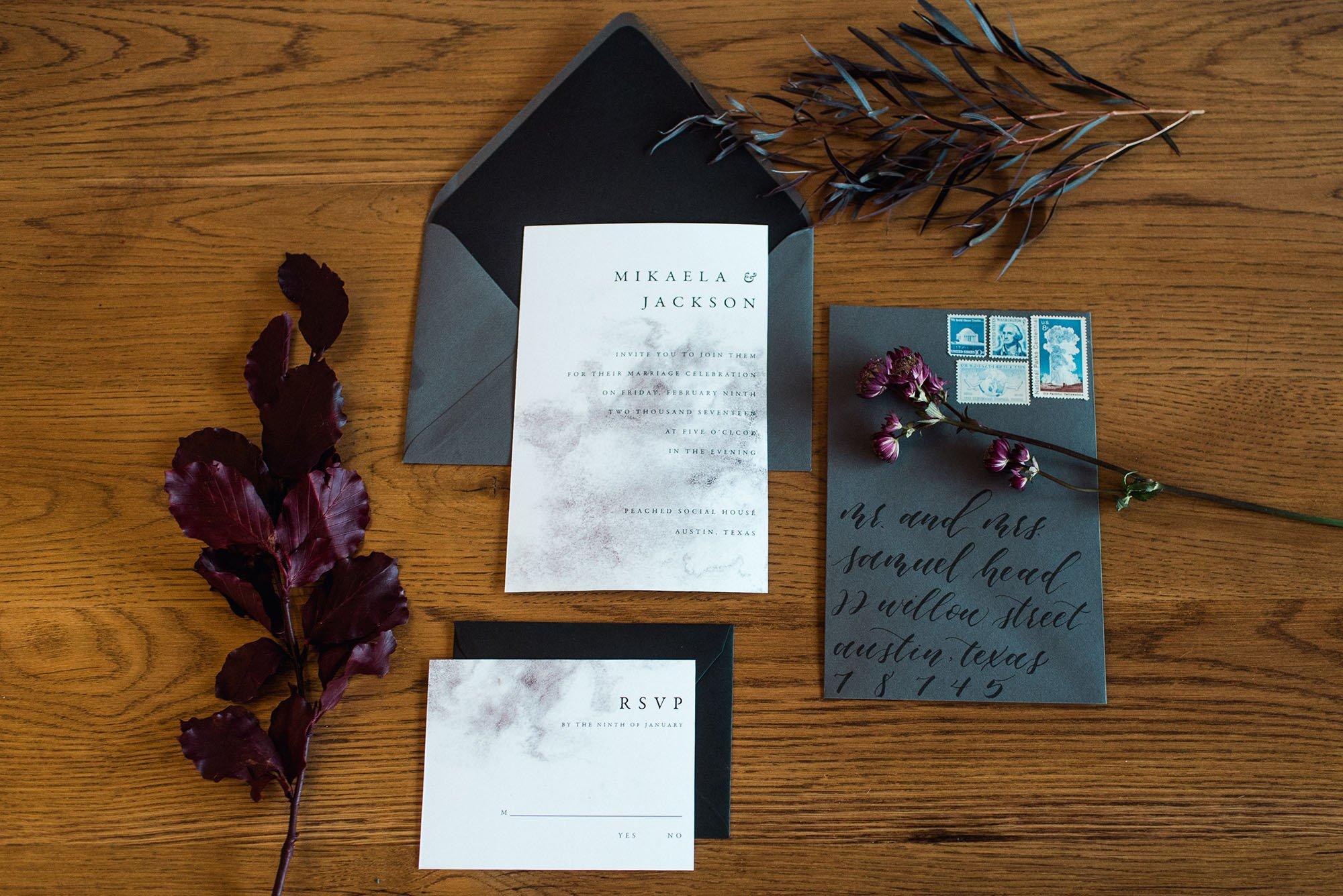 dark and moody wedding invitation lay flat,