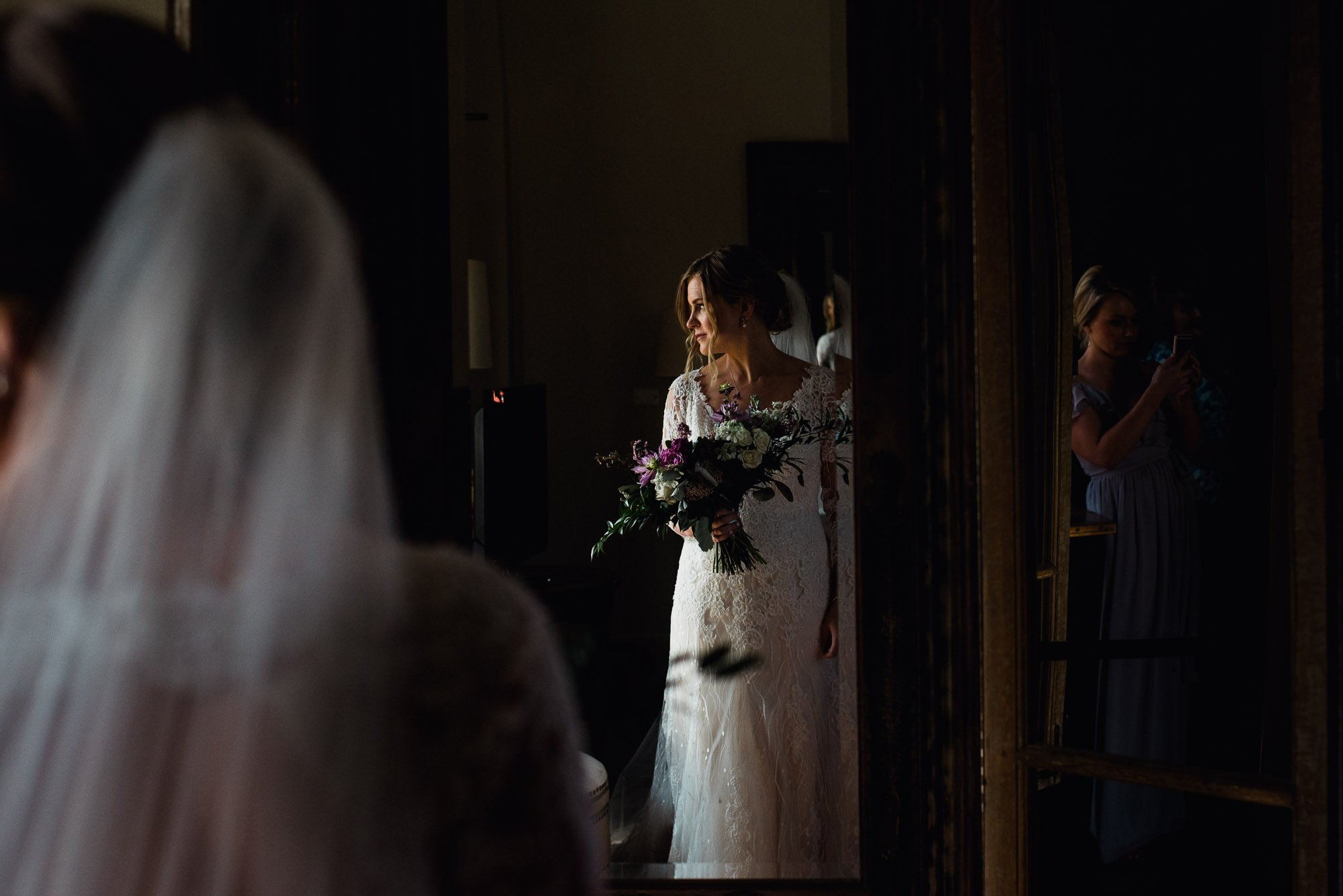 bride getting ready next to a big window at her henkel hall wedding, getting ready photographs