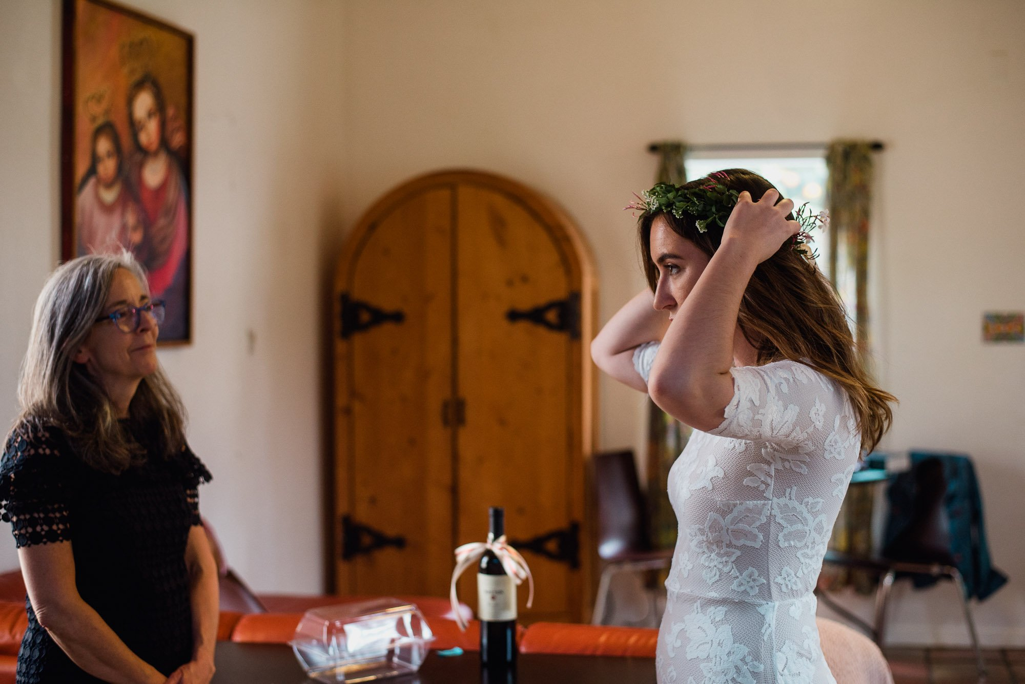 bride wearing a flower crown gets ready alone before her backyard wedding at the king william manor in san antonio