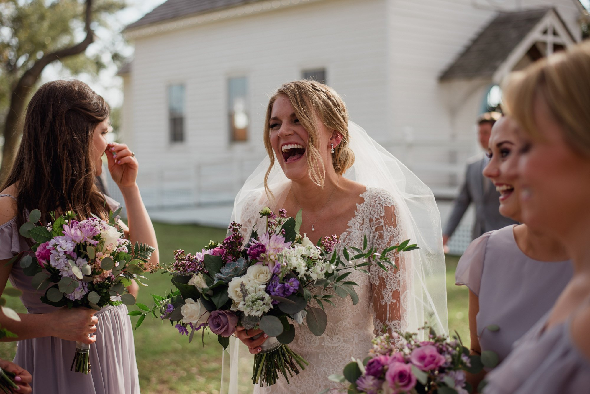 bride laughing with her wedding party outside at a round top wedding