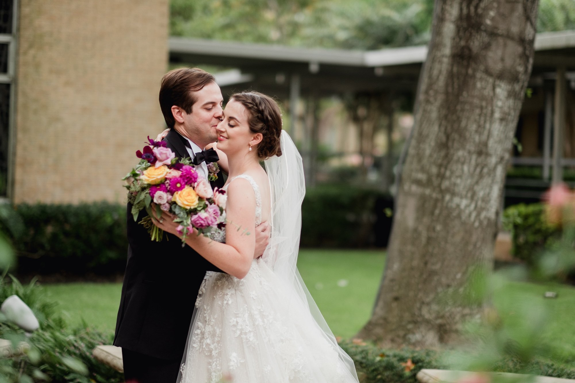catholic wedding with first look, first look at st. louis king of france church, austin downtown wedding, emotional wedding photography in austin texas, kiss on the cheek during a couples' first look at a colorful austin weding