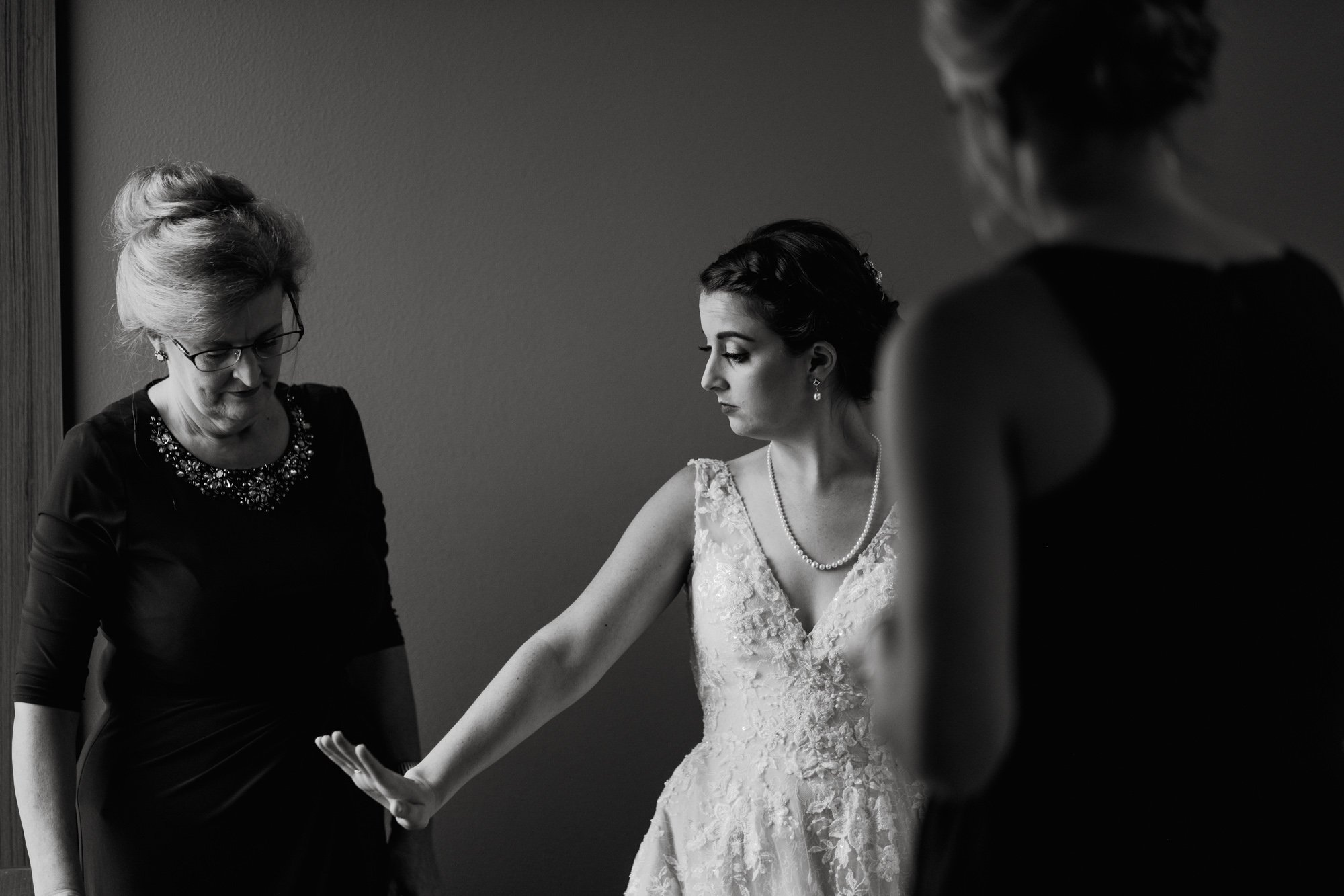 bride looks at her ring while her mom and sister gather around her