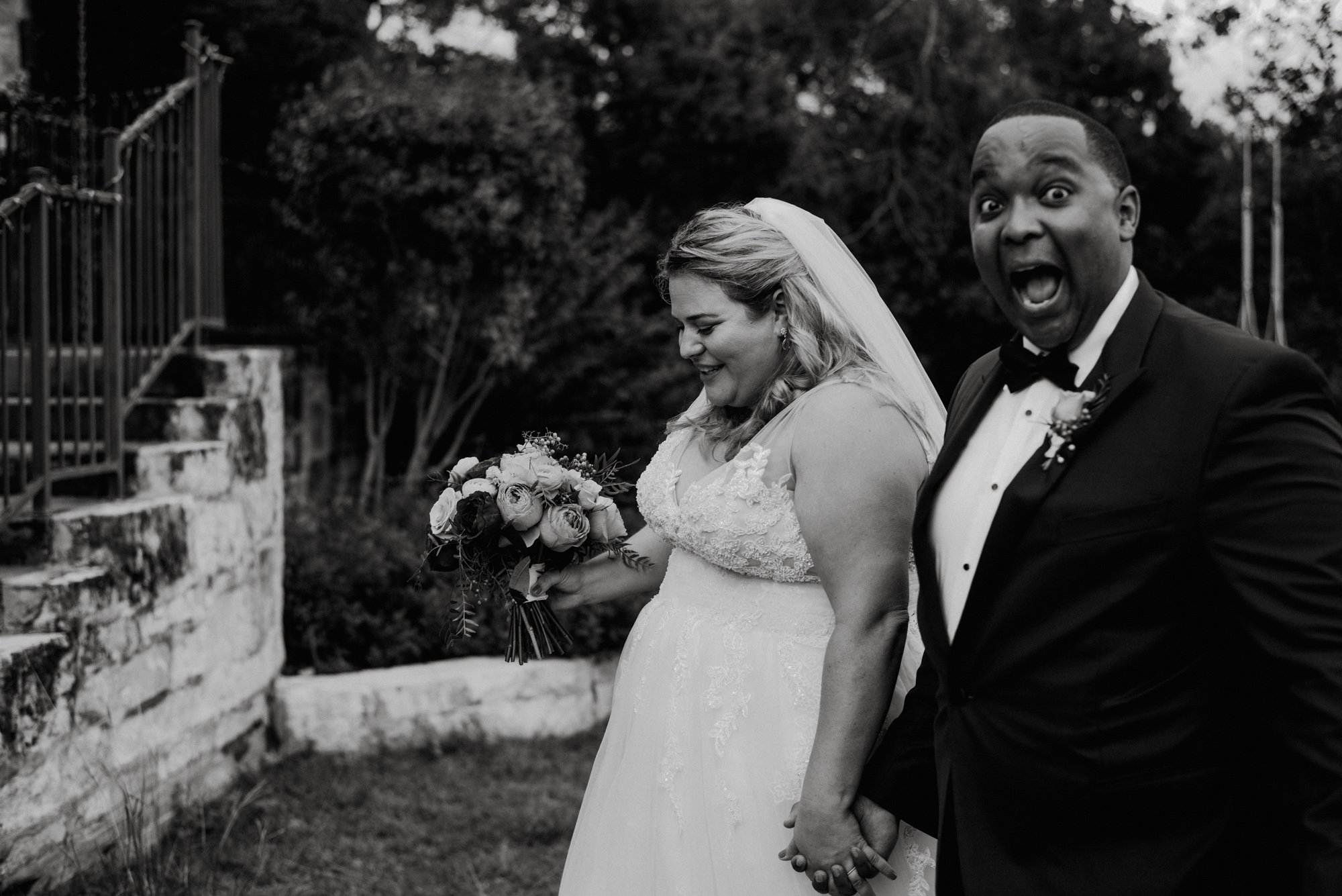 candid photo of groom making face after walking down the aisle, black and white wedding phojournalism