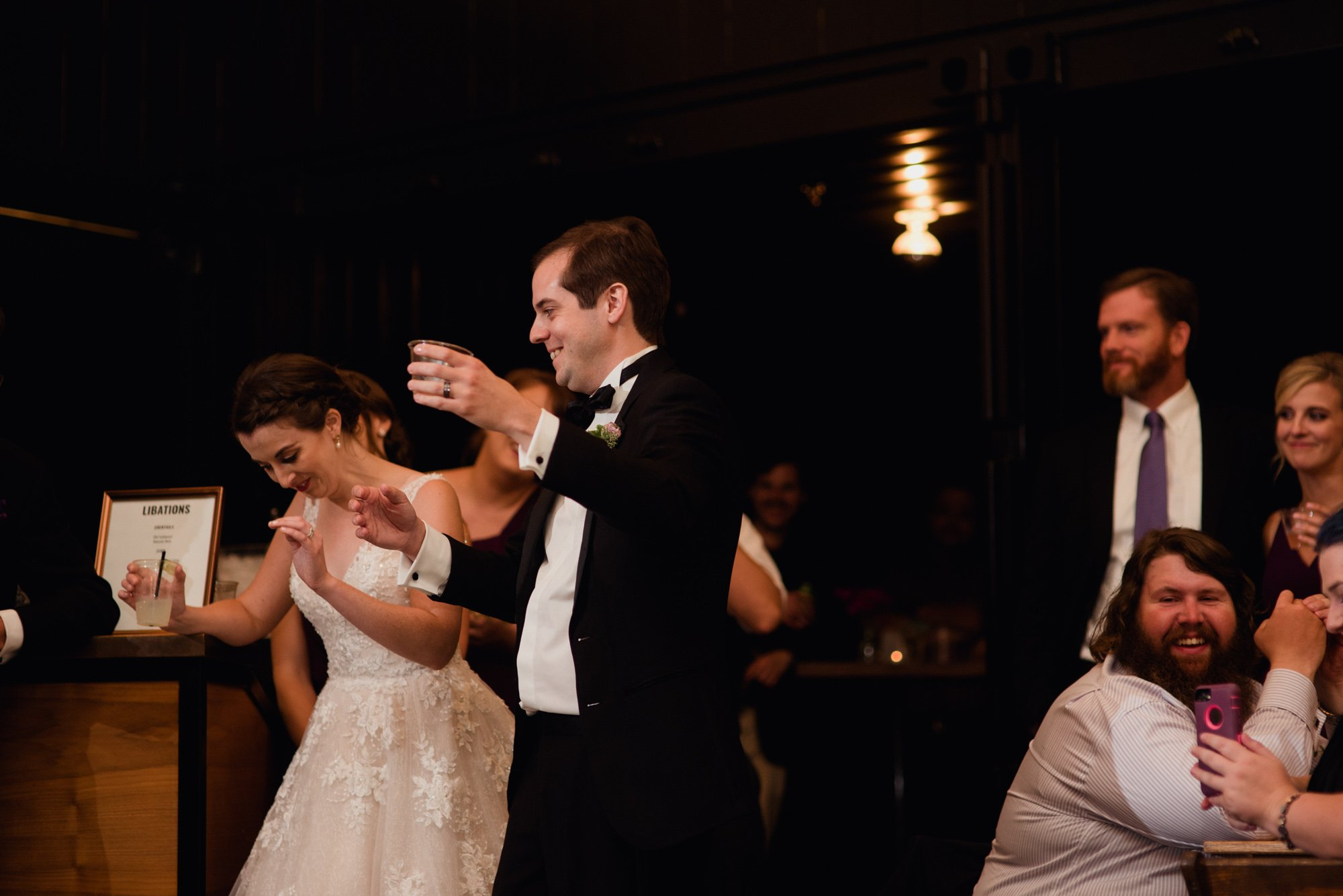 bride and groom reactions to toasts at a peached social house indoor wedding reception
