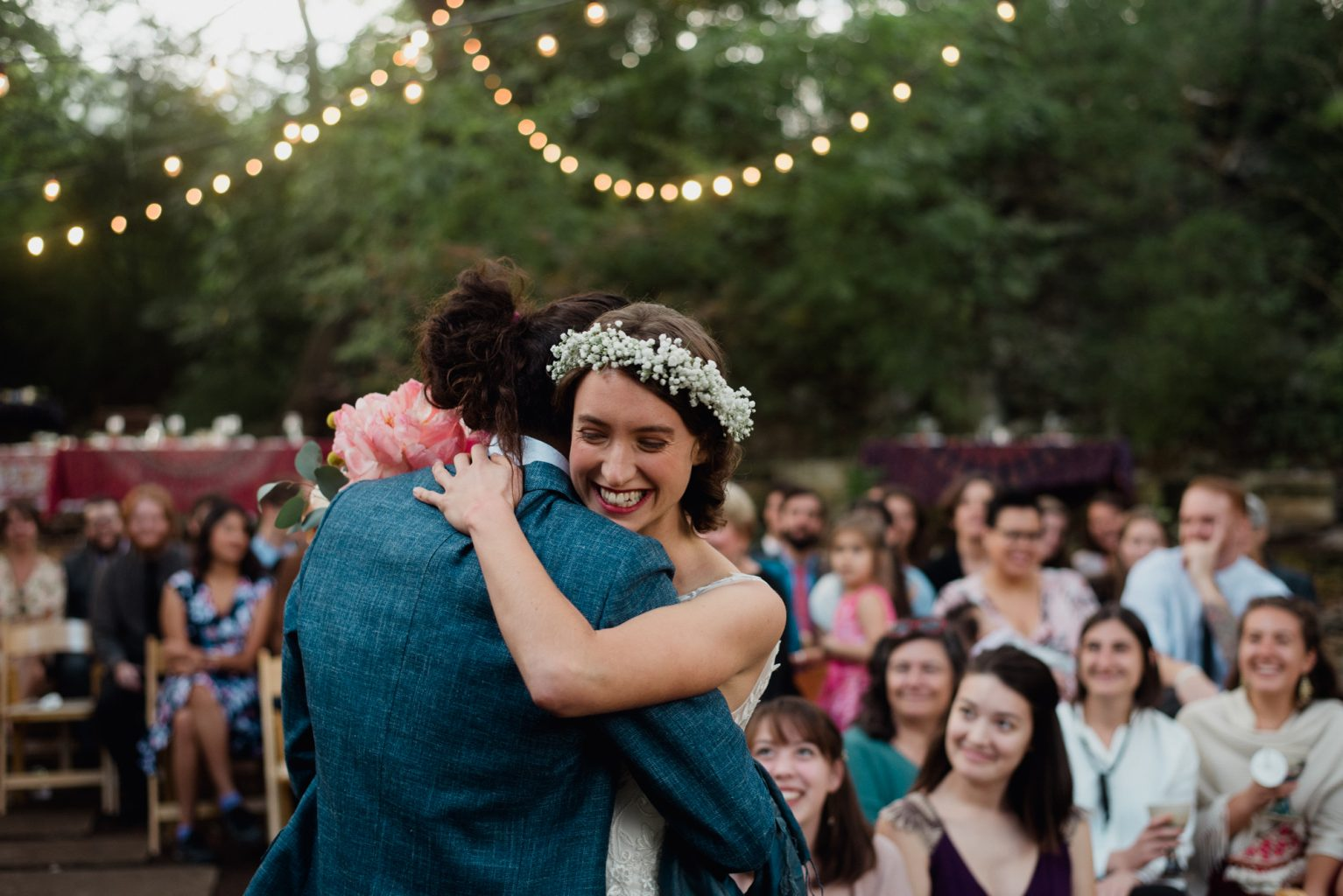 bride and groom embrace with smiles at their backyard Austin wedding in the fall