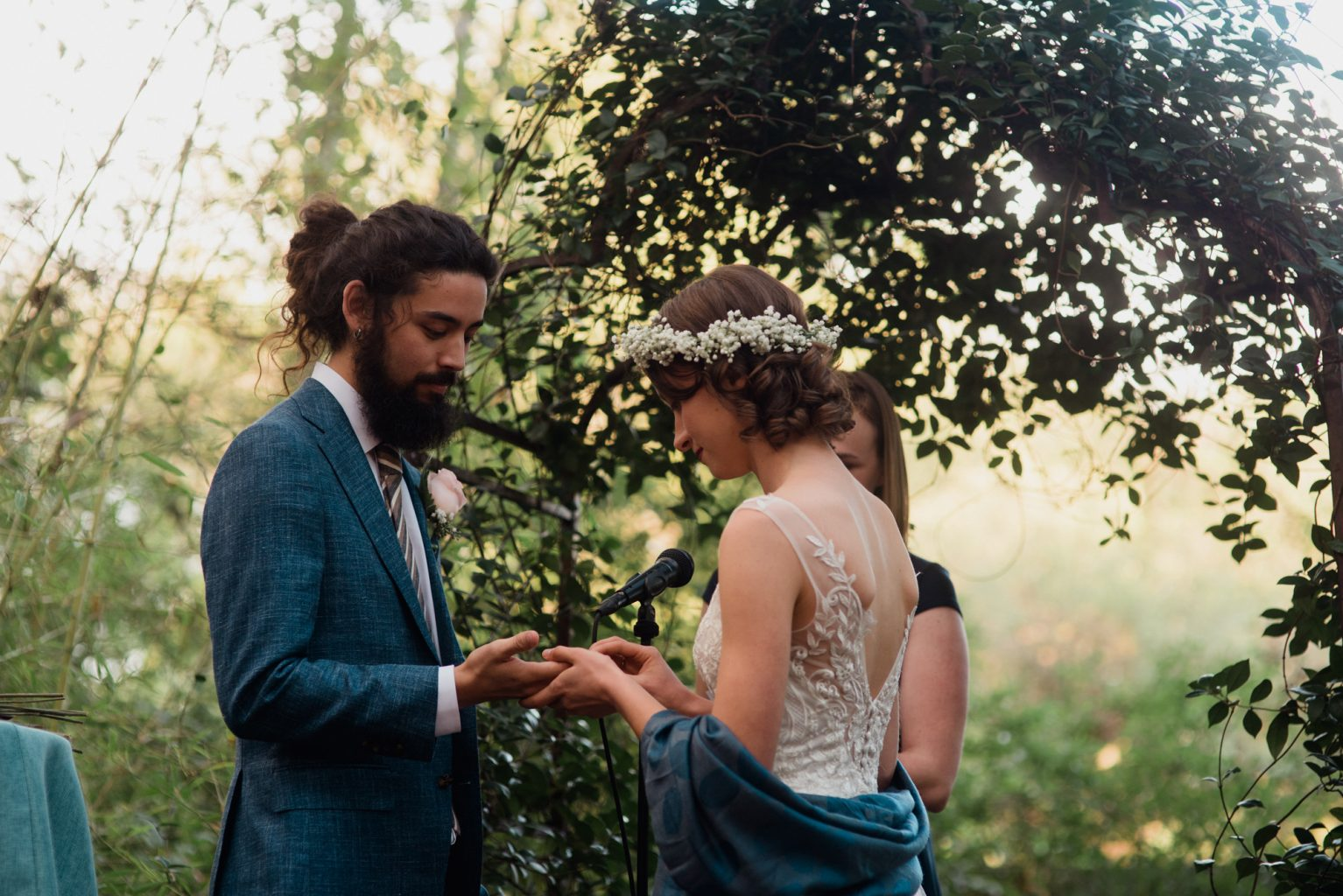 bride and groom exchange rings in front of a greenery archway at their Fall Austin, Texas wedding