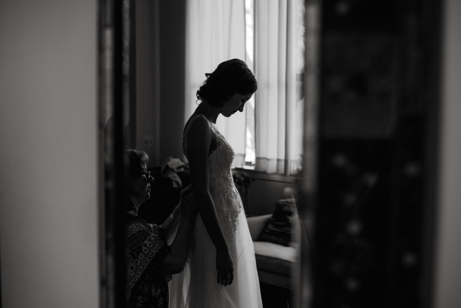 bride silhouetted against a window gets ready for her Austin wedding, storytelling wedding photography in Austin, Texas wedding photographer